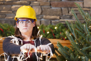 A woman in a hard hat attempting to decorate for the holidays.