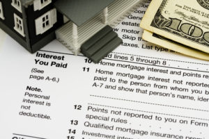 Picture of mortgage interest tax form with a toy house and money on top.