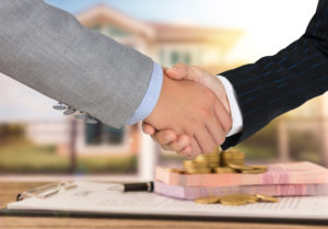 A high quality mortgage loan officer shaking hands with a new homeowner.