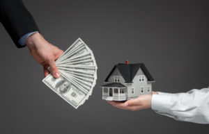 A stack of money being used to buy a model house.