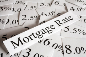 Piece of paper saying mortgage rates on top of other paper showing various rates.