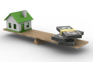 A wooden scale balancing money and a home to symbolize the question of waiting to apply for a mortgage.