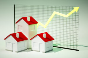 3 Houses with an upward graph in the background to signify the housing trends in 2017.
