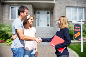 Couple shaking hands with their realtor as they buy their first home.
